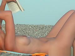Nudist girls splashing around and playing in shallow water
