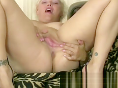 Kelly strips and finger fucks her shaved pussy.