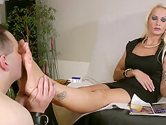 Platinum blonde tattooed mistress in black dress gets her feet worshiped by naked fat slave